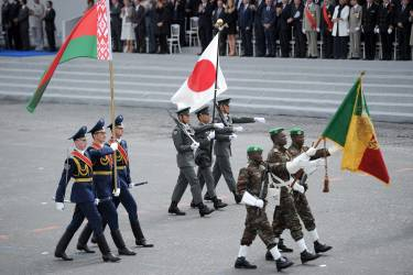 Belarusian (L), Japanese (C) and Beninese soldiers parade on July 14, 2014 on the Champs Elysees avenue in Paris during the annual Bastille Day military parade.  France has issued an unprecedented invitation to all 72 countries involved in World War I to take part in its annual Bastille Day military parade.  AFP PHOTO / STEPHANE DE SAKUTIN