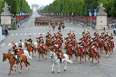 Republican Guards on horseback ride down the Champs-Elysees avenue during the annual Bastille Day military parade in Paris, on July 14, 2014.  AFP PHOTO / ALAIN JOCARD