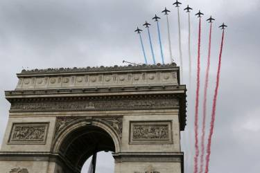 France's national colours trail above the Arc de Triomphe during the traditional Bastille Day parade on the Champs Elysees in Paris, July 14, 2014. The year 2014 marks the 100th anniversary of the start of the First World War.   REUTERS/Gonzalo Fuentes (FRANCE  - Tags: MILITARY ANNIVERSARY POLITICS)