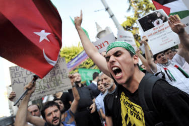 A protester gestures and shouts slogans during a demonstration against Israel's bombing of Gaza on Istiklal avenue in Istanbul, Turkey, on July 17, 2014. Israeli air strikes in Gaza killed four children on July 17, medics said, after a humanitarian lull in a 10-day conflict that has killed 237 Palestinians. AFP PHOTO / OZAN KOSE