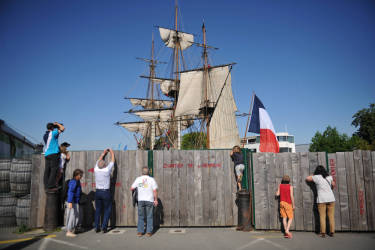 Curious check out from behind a fence as crew members hoist the sails of the replica of French frigate Hermione during a ceremony in Rochefort, western France, on May 17, 2014. The original Hermione was a 12-pounder Concorde class frigate of the French Navy, which in 1780 ferried General Lafayette to the United States to allow him to rejoin the American side in the American Revolutionary War. The replica is to set sail for a transatlantic crossing in 2015. AFP PHOTO / PHOTO XAVIER LEOTY
