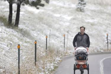 Mike West jogs with his baby after the season's first snow fell over Boulder, Colo., Friday, Sept. 12, 2014. Boulder saw less than an inch of snow overnight, about a month earlier than the average first snow on the front range of the Colorado Rockies, according to the National Weather Service. (Brennan Linsley)