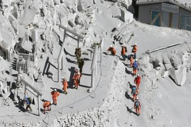 Firefighters advance to rescue climbers near the peak of Mount Ontake in central Japan, Sunday, Sept. 28, 2014. Mount Ontake erupted shortly before noon Saturday, spewing large white plumes of gas and ash high into the sky and blanketing the surrounding area in ash. Rescue workers on Sunday found more than 30 people unconscious and believed to be dead near the peak of an erupting volcano, a Japanese police official said. (AP Photo/Kyodo News) JAPAN OUT, MANDATORY CREDIT