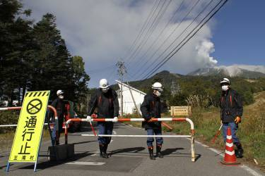 Otaki Village firefighters control access to a road leading to Mount Ontake, background right, as it continues to erupt Sunday, Sept. 28, 2014, in Otaki Village, Nagano prefecture, Japan. A Japanese military helicopter rescued three people Sunday morning from the spectacular volcanic eruption that sent officials scrambling to reach many more injured and stranded on the mountain. Mount Ontake in central Japan erupted shortly before noon Saturday, catching mountain climbers by surprise and injuring at least 34, including 12 seriously, according to Japan's Fire and Disaster Management Agency. The tally was lower than reported by local officials earlier, but the disaster agency warned that the numbers could still change. (AP Photo/Koji Ueda)