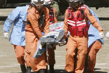 ATTENTION EDITORS - VISUAL COVERAGE OF SCENES OF INJURY OR DEATH  Firefighters carry a hiker from a helicopter after a rescue operation near the peak of Mt. Ontake in Kiso town, Nagano prefecture, central Japan in this September 28, 2014 photo taken and released by Kyodo. More than 30 people were feared dead on Sunday near the peak of the Japanese volcano that erupted a day earlier, sending a huge cloud of ash and rock tumbling down its slopes, while packed with hikers. Mandatory credit.   REUTERS/Kyodo (JAPAN - Tags: DISASTER ENVIRONMENT) ATTENTION EDITORS - FOR EDITORIAL USE ONLY. NOT FOR SALE FOR MARKETING OR ADVERTISING CAMPAIGNS. THIS IMAGE HAS BEEN SUPPLIED BY A THIRD PARTY. THIS PICTURE WAS PROCESSED BY REUTERS TO ENHANCE QUALITY. AN UNPROCESSED VERSION WILL BE PROVIDED SEPARATELY. MANDATORY CREDIT. JAPAN OUT. NO COMMERCIAL OR EDITORIAL SALES IN JAPAN. YES