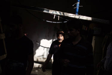 A group of neighbors of Bab el-Tabaneh district in Trip walks inside a damaged building after the clashes. Tuesday, October 28, 2014. Diego Ibarra Sánchez for LE MONDE