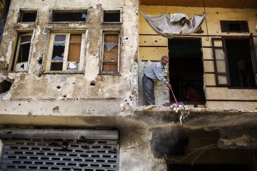 Abu Firis cleans his home following clashes between Lebanese soldiers and Islamist gunmen in Tripoli, northern Lebanon.  He dragged with his family on the ground to keep them safe from the bulletsTuesday, October 28, 2014. Diego Ibarra Sánchez for LE MONDE
