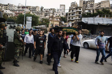 Civilians carry a coffin and walk past a Lebanese army soldier patrolling on an armored vehicles after being deployed to tighten security following clashes between Lebanese soldiers and Islamist gunmen in Tripoli, northern Lebanon. Tuesday, October 28, 2014. Diego Ibarra Sánchez for LE MONDE
