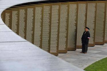 """Maurice Felicien, a guard of honor of the ossuary, poses at the new war memorial at Notre Dame de Lorette, an elliptical ring engraved with the names of the 580,000 men who died in northern France during the First World War, in Ablain-Saint-Nazaire November 5, 2014. The memorial, paying respect to fighters of all nationalities who perished in this land between 1914 and 1918, is on the edge of the Notre-Dame de Lorette French war cemetery, itself containing the bodies of over 40,000 soldiers. Designed by the architect Philippe Prost, the """"Ring of Memory"""" will be inaugurated on Armistice Day on November 11 by French President, in the presence of dignitaries from other countries involved in the conflict. The year 2014 marks the centennial commemoration for the soldiers who fought in the First World War (WWI).  REUTERS/Pascal Rossignol (FRANCE - Tags: MILITARY ANNIVERSARY CONFLICT)"""