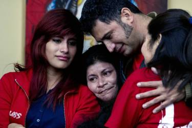 Oscar Alfaro embraces his wife Enriquta Juarez and his daughter Gelin Alfaro after President Barack Obama's televised immigration speech at Casa de Maryland in Hyattsville, Md., Thursday, Nov. 20, 2014. Obama announced that millions of illegal immigrants will gain protections from deportation under a plan that would bypass Congress. (AP Photo/Jose Luis Magana)