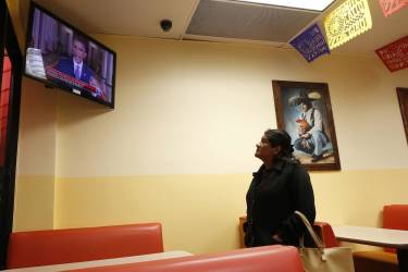 A woman watches U.S. President Barack Obama's White House speech on immigration at a restaurant in Huntington Park, California, November 20, 2014. Obama imposed the most sweeping immigration reform in a generation on Thursday, easing the threat of deportation for about 4.7 million undocumented immigrants and setting up a clash with Republicans. REUTERS/Lucy Nicholson   (UNITED STATES - Tags: POLITICS SOCIETY IMMIGRATION)