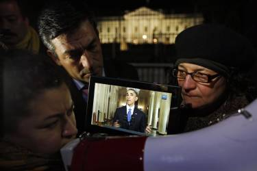 Rosa Lozano, from Washington, left, translates the speech into Spanish as Lita Trejo, from El Salvador, and Texas Democratic State Rep. Ramon Romero, listen to President Obama's speech on a tablet, during a demonstration in front of the White House in Washington, Thursday, Nov. 20, 2014. President Barack Obama announced executive actions on immigration during a nationally televised address. (AP Photo/Alex Brandon)