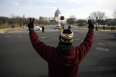 A lone marcher at the front of the national Justice For All march against police violence holds his hands up towards the U.S. Capitol building, in Washington December 13, 2014. Civil rights activist Rev. Al Sharpton is leading the march following a New York grand jury decision not to indict a white policeman in the chokehold death of an unarmed black man.  REUTERS/Jim Bourg  (UNITED STATES - Tags: POLITICS CRIME LAW CIVIL UNREST)