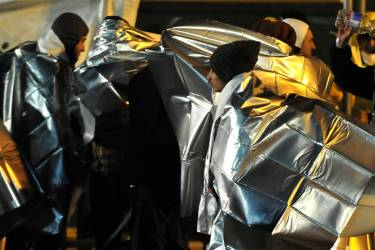 """Some 500 Syrian would be immigrants receive first aid as they disembark from the Ezadeen ship at Corigliano harbour on January 2, 2015. Italian coastguards have narrowly prevented two disasters this week off the country's southern coast involving so-called """"ghost ships"""", which seem to have originated in Turkey. The EU vowed to fight people smugglers' new tactic of abandoning """"ghost ships"""" full of migrants off European coasts. AFP PHOTO/ALFONSO DI VINCENZO"""