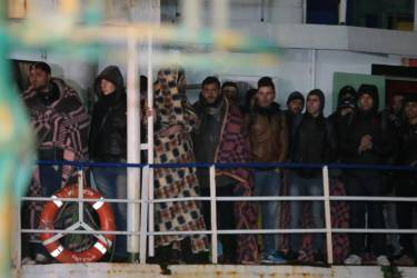 The cargo ship Ezadeen, carrying hundreds of migrants, arrives at the southern Italian port of Corigliano, Italy, late Friday, Jan. 2, 2015. The cargo ship was stopped with about 450 migrants aboard after smugglers sent it speeding toward the coast in rough seas with no one in command. Italian authorities lowered engineers and electricians onto the wave-tossed ship by helicopter to secure it, and the Icelandic Coast Guard towed it to the Italian port of Corigliano late Friday night. Smugglers who bring migrants to Europe by sea appear to have adopted a new, more dangerous tactic: cramming hundreds of them onto a large cargo ship, setting it on an automated course to crash into the coast, and then abandoning the helm. (AP Photo/Antonino D'Urso)