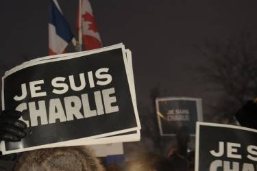 """People holds signs reading """"I  Am Charlie"""" during a vigil January 7, 2015 outside  City Hall in Montreal, Canada  for the victims of the shooting at the office of the French satirical magazine Charlie Hebdo.  Twelve people were killed when several gunmen opened fire at Charlie Hebdo's headquarters in Paris, France on January 7th. AFP PHOTO / MARC BRAIBANT"""