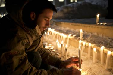 A man lights a candle during a demonstration in solidarity with those killed in an attack at the Paris offices of the weekly newspaper Charlie Hebdo  in Kosovo capital Pristina, Wednesday, Jan. 7, 2015. Masked gunmen stormed the the satirical newspaper methodically killing at least 12 people Wednesday, including the editor, before escaping in a car. It was France's deadliest postwar terrorist attack. (AP Photo/Visar Kryeziu)