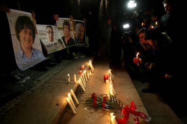 Albanian journalists light candles, in  Tirana, Albania, Wednesday, Jan. 7, 2015,  in solidarity with those killed in an attack at the Paris offices of the weekly newspaper Charlie Hebdo. Masked gunmen stormed the the satirical newspaper methodically killing at least 12 people Wednesday, including the editor, before escaping in a car. It was France's deadliest postwar terrorist attack. (AP Photo/Hektor Pustina)