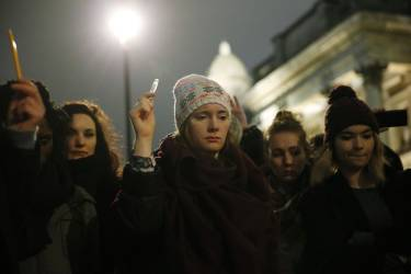 People raise pens during a vigil to pay tribute to the victims of a shooting by gunmen at the offices of weekly satirical magazine Charlie Hebdo in Paris, at Trafalgar Square in London January 7, 2015. Hooded gunmen stormed the Paris offices of a satirical magazine known for lampooning Islam and other religions on Wednesday, killing at least 12 people in the most deadly militant attack on French soil in decades. REUTERS/Suzanne Plunkett (BRITAIN - Tags: POLITICS CRIME LAW CIVIL UNREST MEDIA)