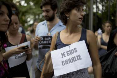 """People stand outside France's embassy wearing signs that read in French """"I am Charlie"""" in solidarity with those killed in an attack at the Paris offices of the weekly newspaper Charlie Hebdo in Buenos Aires, Argentina, Wednesday, Jan. 7, 2015. Masked gunmen stormed the the satirical newspaper that caricatured the Prophet Muhammad, methodically killing 12 people Wednesday, including the editor, before escaping in a car. It was France's deadliest postwar terrorist attack. (AP Photo/Natacha Pisarenko)"""
