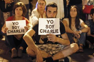 """People hold prints reading """"I am Charlie"""" during a vigil to pay tribute to the victims of a shooting by gunmen at the offices of weekly satirical magazine Charlie Hebdo in Paris, at Kennedy Park in Lima, January 7, 2015. Hooded gunmen stormed the Paris offices of the magazine known for lampooning Islam and other religions, shooting dead at least 12 people, including two police officers, in the worst militant attack on French soil in decades. REUTERS/Enrique Castro-Mendivil (PERU - Tags: CRIME LAW MEDIA CIVIL UNREST)"""