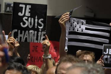 """People hold signs reading """"I am Charlie"""" during a demo in tribute to the 17 victims of a three-day killing spree in Paris by homegrown Islamists, outside the French Embassy in Buenos Aires, on January 11, 2015. The tribute took place in support of the Paris rally in which more than a million people flooded Paris on Sunday against terrorism, led by dozens of world leaders walking arm in arm as cries of """"Freedom"""" and """"Charlie"""" rang out. The killings began on January 7 with an assault on the Charlie Hebdo satirical magazine in Paris. AFP PHOTO / ALEJANDRO PAGNI"""